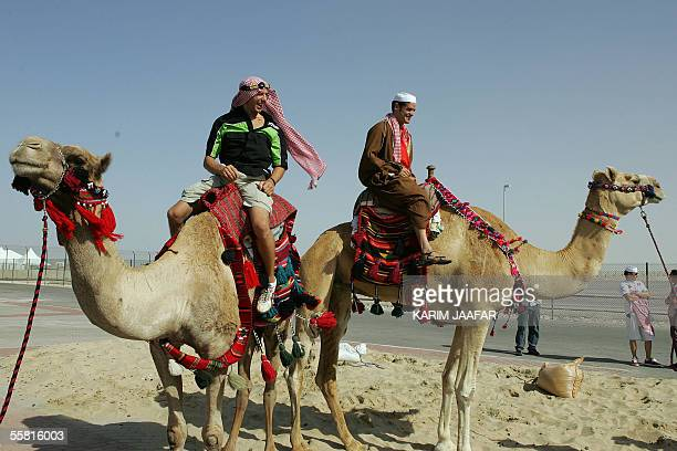 French rider Frenchman Olivier Jacques and Carlos Checa of Spain take a camel ride during a visit to a cultural tent at the Losail International...