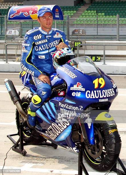 French rider Olivier Jacque poses with his new of Gauloises Yamaha Tech 3 at the pits of the Sepang International Circuit prior to the first practice...