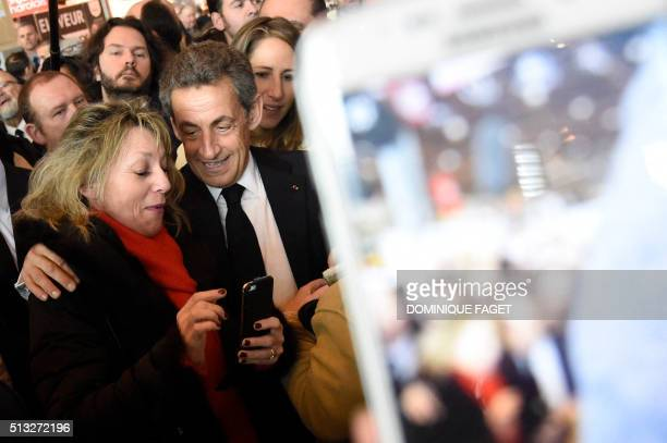 French rightwing Les Republicains party President Nicolas Sarkozy speaks with a supporter after posing for a selfie picture during his visit at the...
