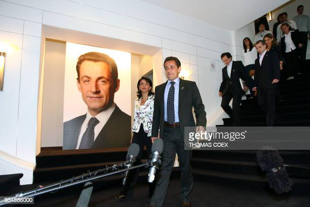 French rightwing party UMP presidential candidate Nicolas Sarkozy arrives for a presser next to Nicole Guedj UMP secretary in charge of humanitarian...