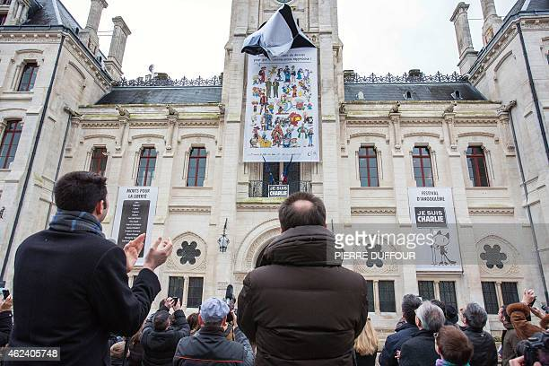 French rightwing UMP party Mayor of Angouleme Xavier Bonnefont claps as a banner is unveiled on the facade of the Hotel de Ville of Angouleme western...