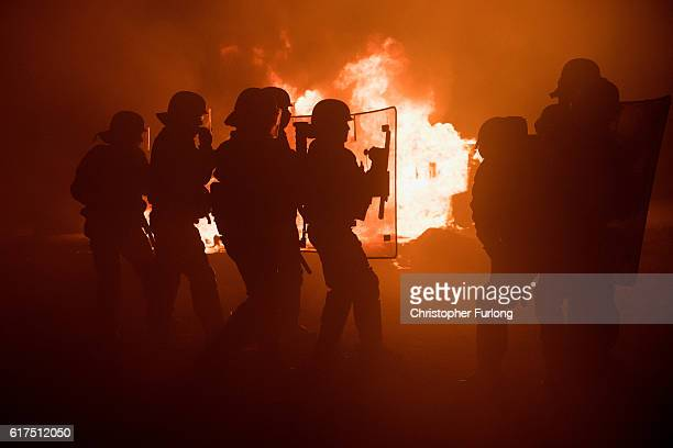 French riot police advance through tear gas and smoke from a fire to disperse migrants throwing stones and lighting fires at the Jungle migrant camp...