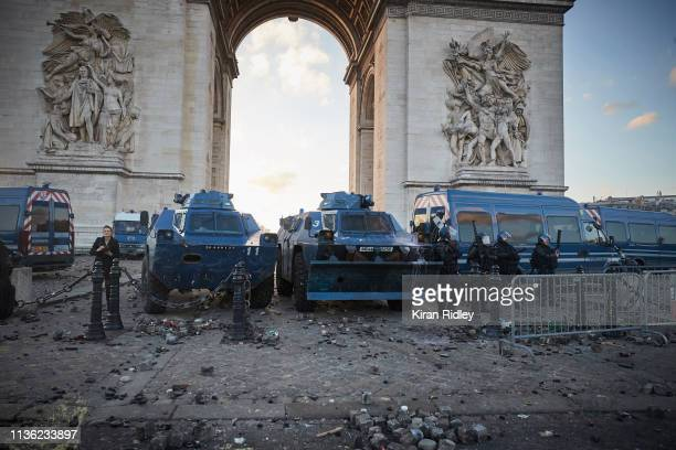 French Riot Police and armoured vehicles stand amidst debris thrown at them near the Arc de Triomphe after violent confrontations during Act 18 of...