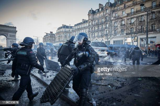French Riot Police clear a smoldering barricade after violent confrontations with Gilets Jaunes or 'Yellow Vest' protestors during Act 18 of protests...