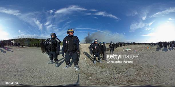 French riot police clear the jungle migrant camp as fires rage across the site believed to have been started by departing migrants on October 26 2016...