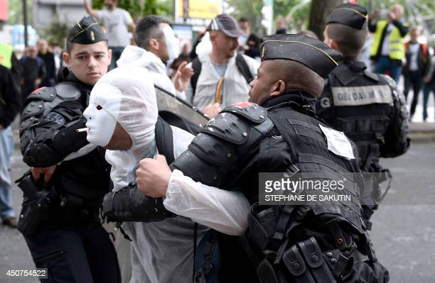French riot police detain an employees of Seita, a subsidiary of Imperial Tobacco, wearing a white suit and mask with a cigarette in his mouth,...
