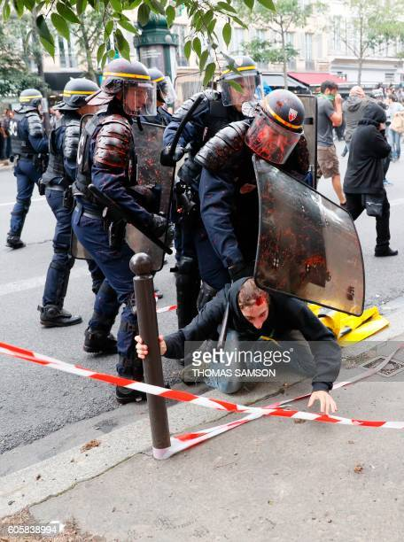 French riot police detain an injured man during a demonstration against the controversial labour reforms of the French government in Paris on...