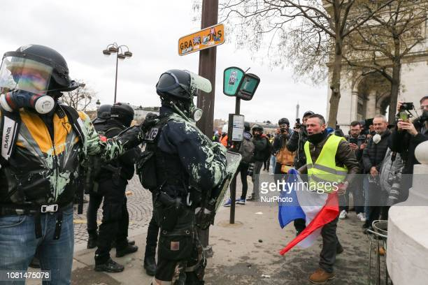 French riot police holding a protective shield are covered in green paint during an antigovernment demonstration called by the Yellow Vest quotGilets...