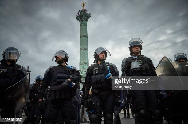 French riot police look towards antigovernment demonstrators at Place de la Bastille during Bastille Day protests on July 14 2020 in Paris France Due...