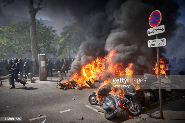 French Riot Police move past a line of burning vehicles during widespread rioting violence and fire in Act 23 of Gilets Jaunes or 'Yellow Vest'...