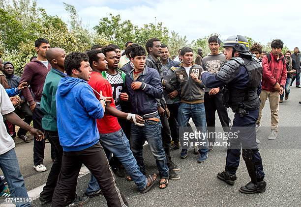 A French riot police officer stands as illegal migrants wait to attempt to hide in lorries heading for England in the French northern harbour of...