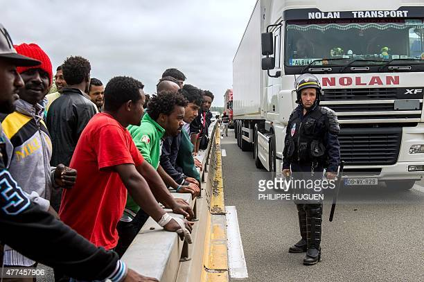 A French riot police officer stands holdings his baton as illegal migrants wait to hide in lorries heading for England in the French northern harbour...