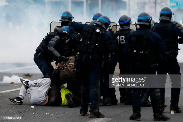 TOPSHOT French riot police officers detain protestors during a demonstration of yellow vests against rising costs of living they blame on high taxes...