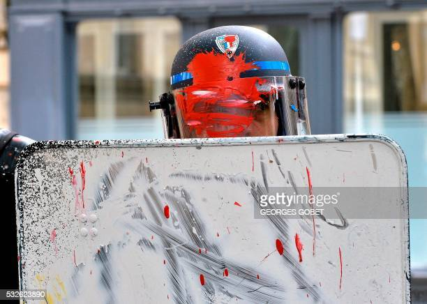 TOPSHOT French riot police officers stand guard after receiving some paint on their uniform during a demonstration to protest against the...