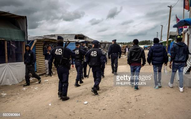 TOPSHOT French riot police patrols inside the 'Jungle' slum in Calais on May 18 2016 The Jungle lies around 40 kilometres from the largest refugee...