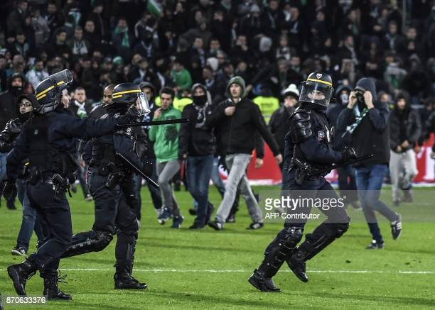 TOPSHOT French riot police run on the pitch where SaintEtienne fans descended during the French L1 football match between AS SaintEtienne and...