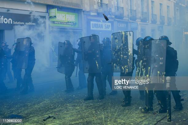 TOPSHOT French riot police sprayed with paint stands sidebyside as members of the yellow vest take part in the 15th consecutive Saturday of...