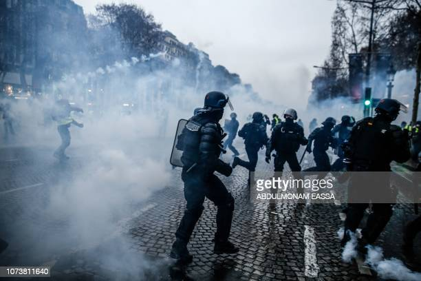 TOPSHOT French riot police stand amid smoke of tear gas during clashes with protesters during a demonstration of yellow vests against rising costs of...