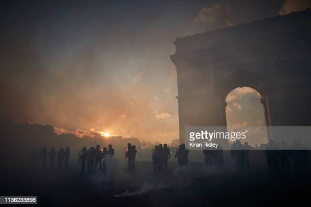 French Riot Police stand amidst clouds of tear gas near the Arc de Triomphe during Gilets Jaunes or 'Yellow Vest' violent protests on March 16 2019...