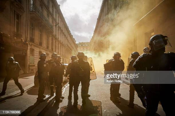 French Riot Police stand amidst tear gas used against Gilets Jaunes or 'Yellow Vest' protestors during Act 17 of protests on the Champs Elysees on...