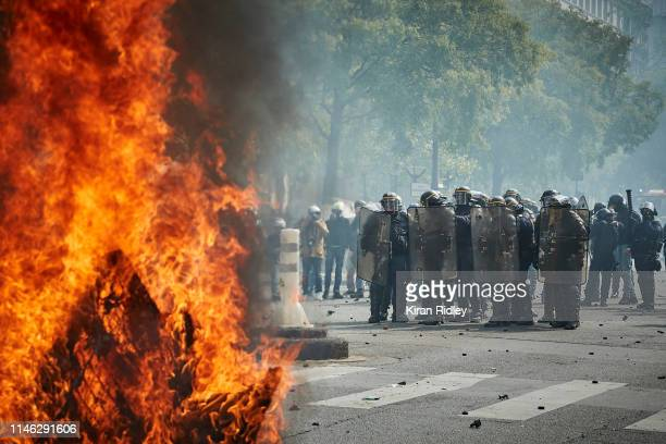 French Riot Police stand in clouds of tear gas near a burning barricade during International Labour Day as demonstrations turn violent on May 01 2019...