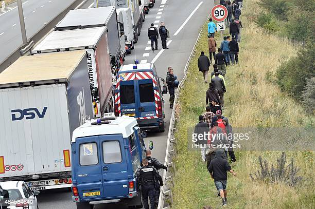 French riot police stand on the side of the road to prevent migrants from approaching lorries on the road leading to the ferry port in Calais...