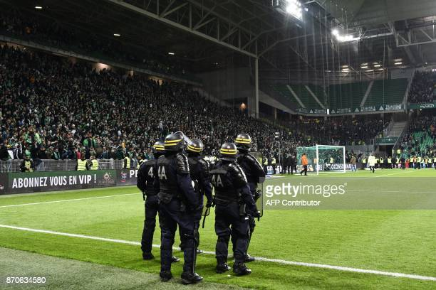 French riot police stand on the sideline of the pitch after fans interrupted the match during the French L1 football match between AS SaintEtienne...