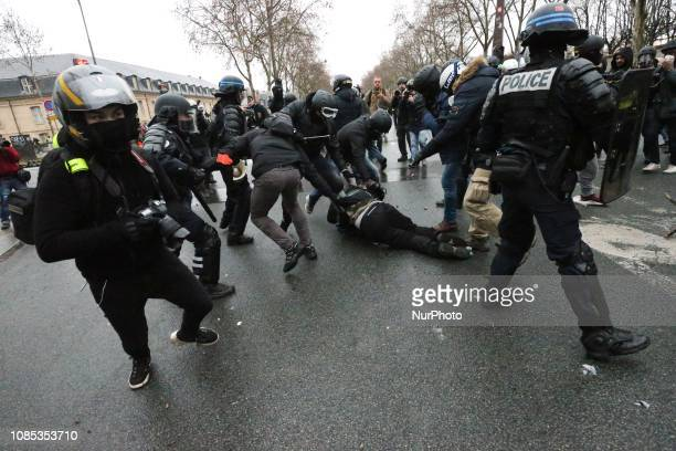 French riot police take a yellow vests protester into custody in front of the Hotel national voice over Invalides in Paris on January 19 2019 during...