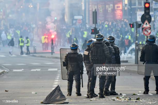 French riot police watch members of the yellow vest as they take part in the 15th consecutive Saturday of demonstrations in Rennes western France on...