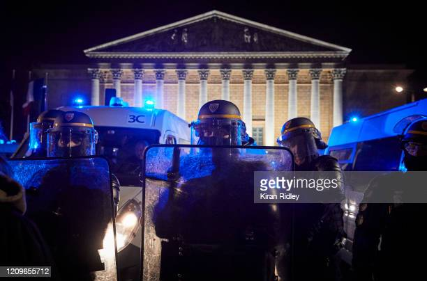 French Riot Policeman holds back a crowd gathered outside the French National Assembly to protest against French Prime Minister Edouard Philippe's...