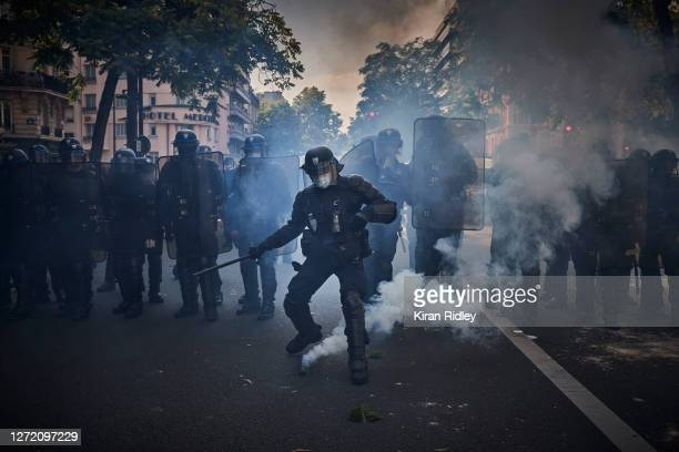 French Riot Policeman kicks a tear gas round back towards protestors as Gilets Jaune protests, after weeks of silence, turned violent on September...