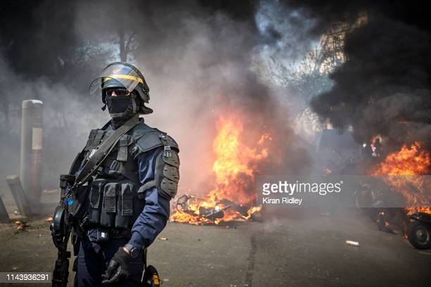 French Riot Policeman stands in front of a row of burning vehicles during Act 23 of Gilets Jaunes or 'Yellow Vest' protests in Paris five days after...