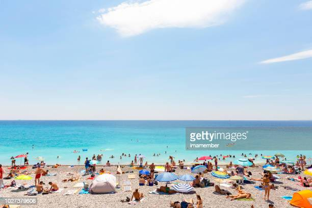french riviera, people on the beach in nice, background with copy space - crowded beach stock pictures, royalty-free photos & images