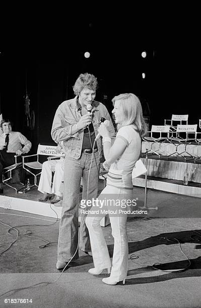 French rock singer Johnny Hallyday and Nicoletta stand together on stage during rehearsals at the Olympia concert hall in Paris