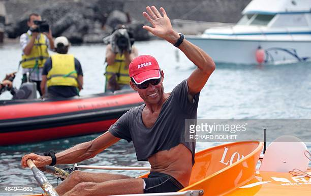 French rower Emmanuel Coindre waves on January 25 2014 while arriving at PortOuest on the French La Reunion overseas island Coindre travelled 7000 km...