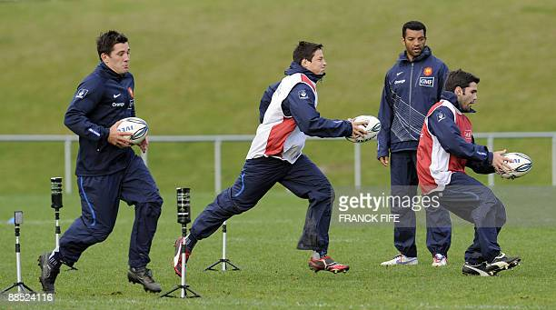 French rugby players Florian Fritz Francois TrinhDuc Dimitri Yachvili pratice with a ball in front assistant coach Emile N'tamack during a training...