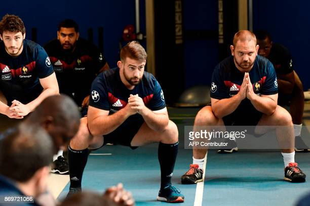 French rugby union national team players Paul Gabrillargues Raphael Chaume and Daniel Kotze stretch in Marcoussis near Paris on November 3 during a...