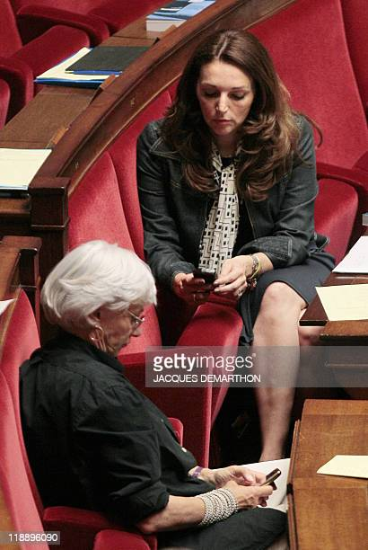 French ruling party UMP MPs Valerie Boyer and François de Panafieu look at their mobile phones during a debate and a vote on France's intervention in...