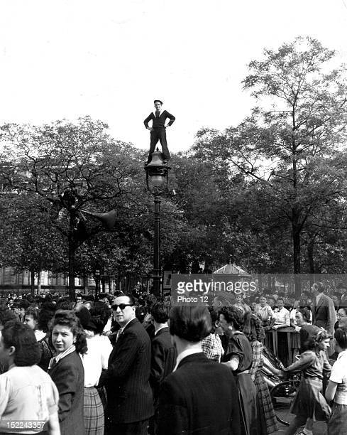 A French sailor arms akimbo stands on a lamppost above the heads of the joyous crowd of Parisians and Allied troops celabrating the final...