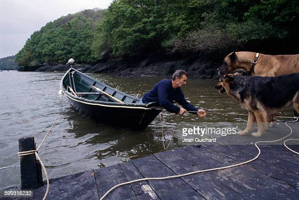 French sailor Eric Tabarly in a rowboat with his dogs at home