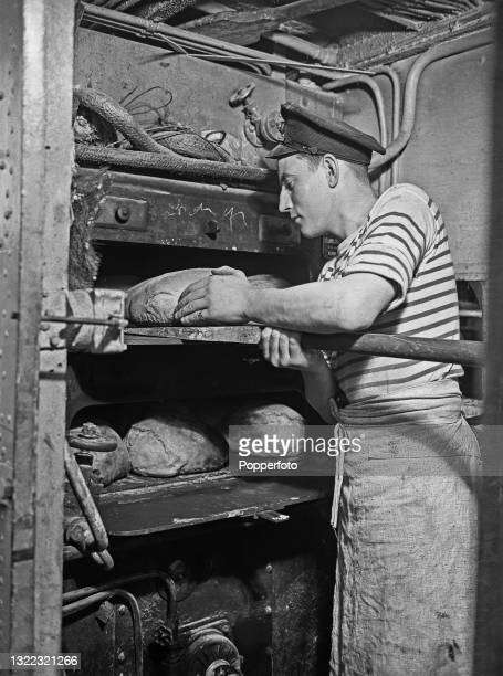 French sailor of the Free French Naval Forces , assigned to the boulangerie, bakes loaves of bread in an oven aboard the French destroyer Le...
