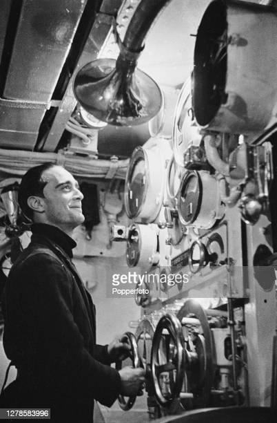 French sailor of the Free French Naval Forces mans the control panel of the battery charging apparatus aboard the French submarine Surcouf on patrol...