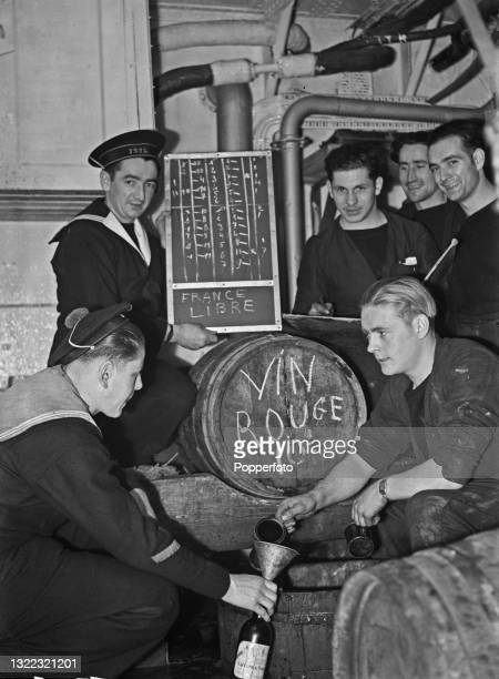 French sailors and mess stewards of the Free French Naval Forces are issued with their rations of red wine aboard the French destroyer Le Triomphant...