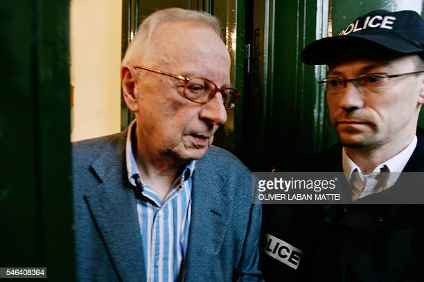 French satirical weekly Canard Enchaine's chief editor Claude Angeli leaves his office passing next to a policeman 11 May 2007 in Paris during a...