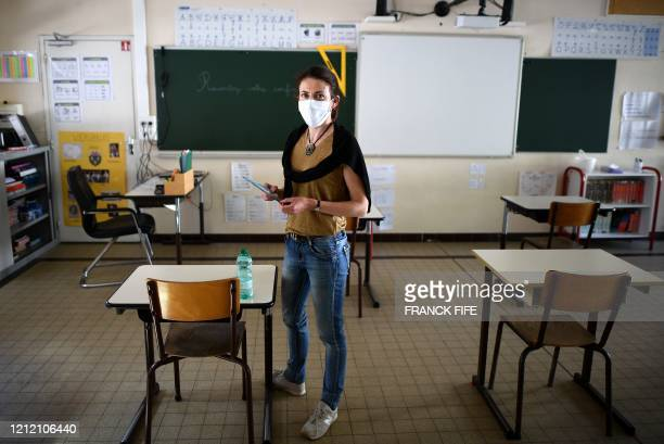 """French school director Delphine Bediou poses in front of a board that reads """"Tell your lockdown"""" in a classroom set up to mark social distancing..."""