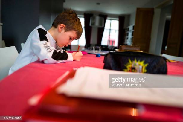 French schoolboy Marceau does his homework as he does school at home while the schools are closed on March 17 in Mulhouse eastern France amid spread...