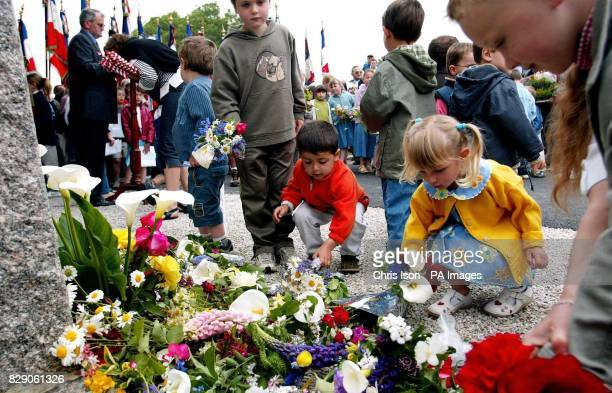 French schoolchildren from Magneville in Normandy lay flowers at a memorial in their village to soldiers of the American 101st Airborne Division who...