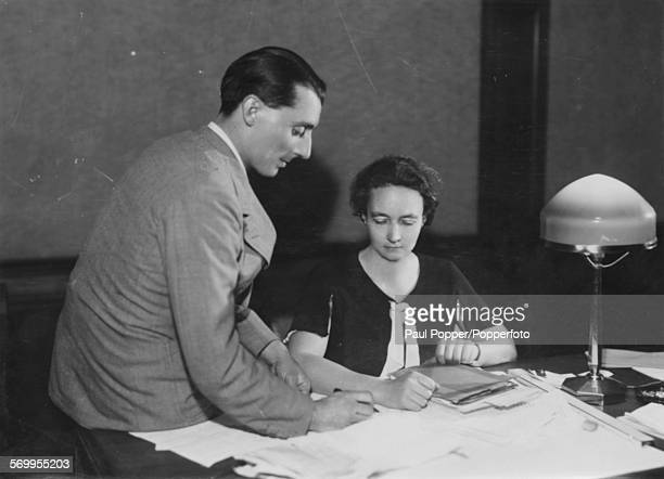 French scientist Irene JoliotCurie and Professor Turpin working on radioactivity research at a desk circa 1925