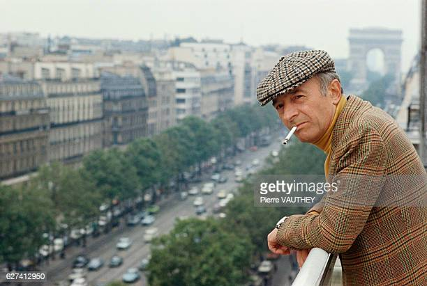 French screenwriter Michel Audiard smokes a cigarette on the balcony of his movie production company overlooking the ChampsElysees and Arc de...