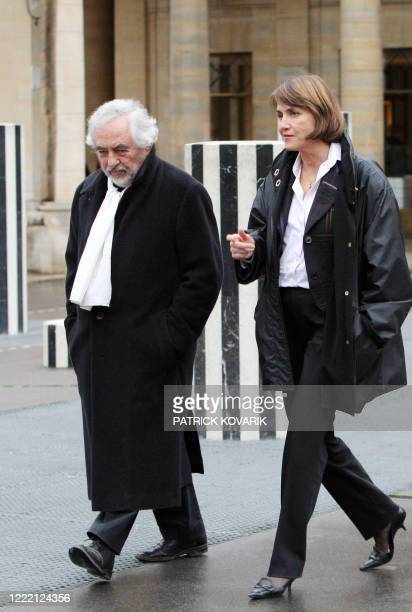 French sculptor Daniel Buren listens to French Culture Minister Christine Albanel after talks focused on the restoration of his culumns as he walks...
